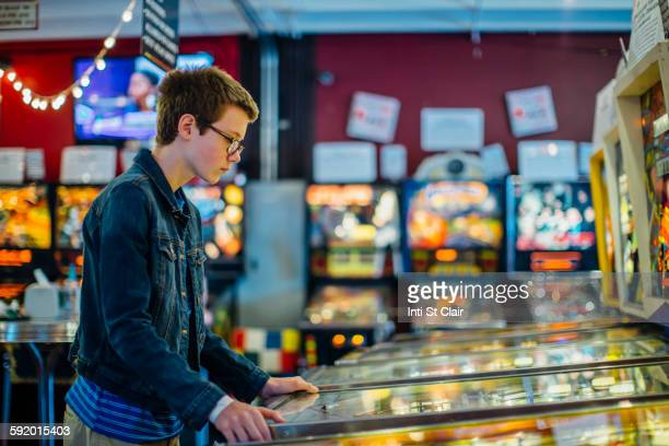 Caucasian teenage boy playing video game in arcade
