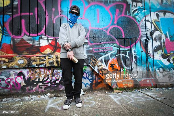 Caucasian teenage boy standing by graffiti wall