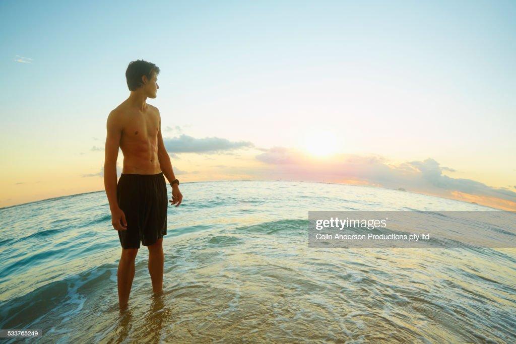 Caucasian teenage boy standing on beach : Foto stock