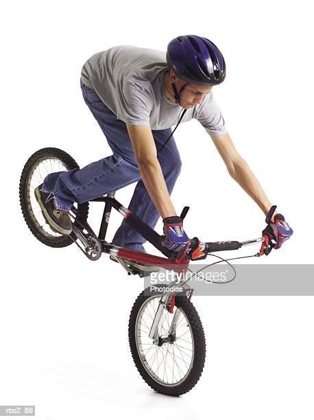 caucasian teenage boy wears blue bike helmet doing a stunt on red bike with rear tire in the air