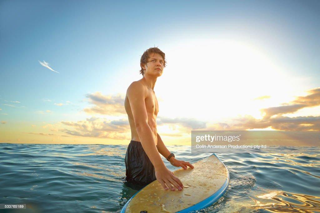 Caucasian teenage boy with surfboard in ocean : Foto stock