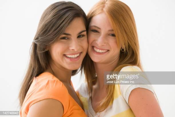 Caucasian teenage friends standing cheek to cheek