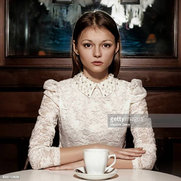 Caucasian teenage girl drinking coffee in restaurant