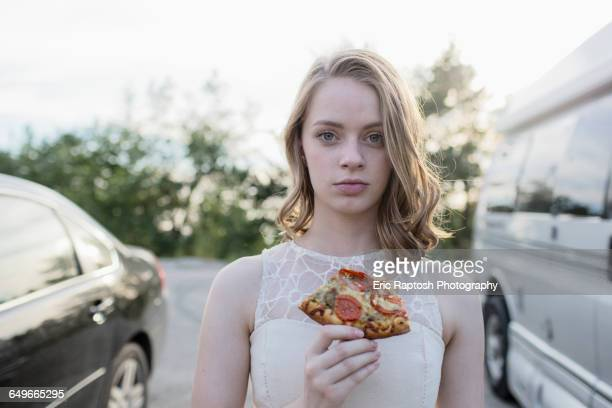 Caucasian teenage girl eating pizza in parking lot