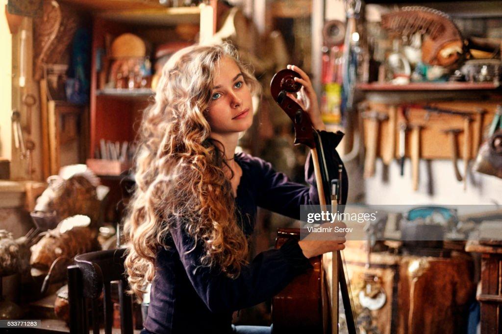 Caucasian teenage girl holding musical instrument in workshop : Foto stock