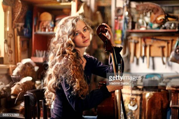 Caucasian teenage girl holding musical instrument in workshop