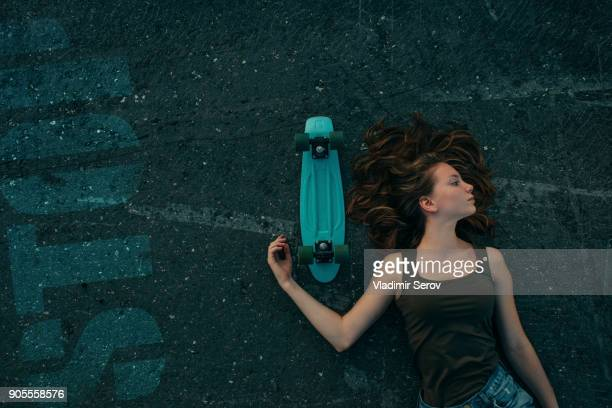 Caucasian teenage girl laying on pavement with skateboard
