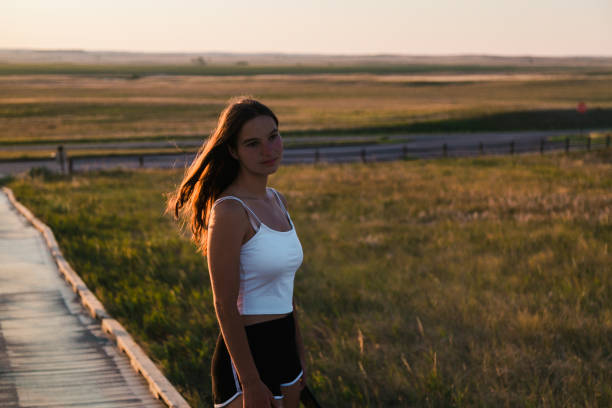 Caucasian teenage girl looking into the distance during sunset,Badlands National Park,South Dakota,United States,USA