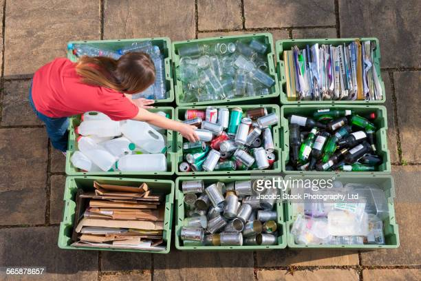 caucasian teenage girl organizing recycling bins - recycling stock pictures, royalty-free photos & images