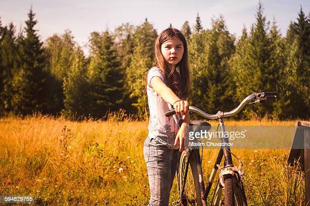 caucasian teenage girl pushing bicycle in field - ein mädchen allein stock-fotos und bilder