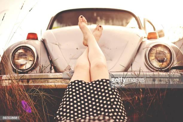 Caucasian teenage girl resting feet on vintage car