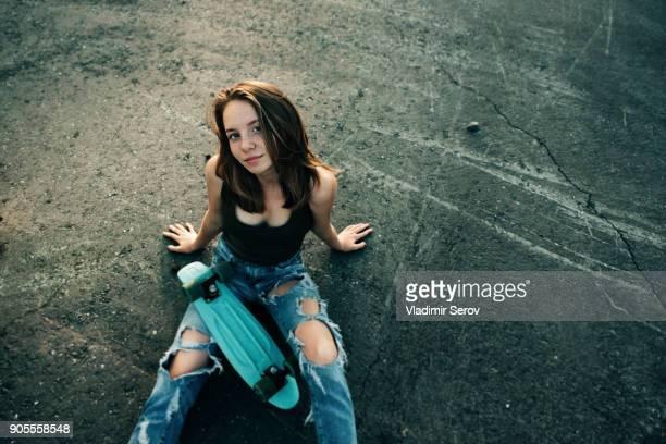 caucasian teenage girl sitting on pavement with skateboard - une seule adolescente photos et images de collection