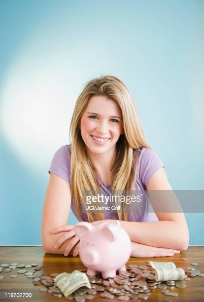 Caucasian teenage girl sitting with coins and piggy bank