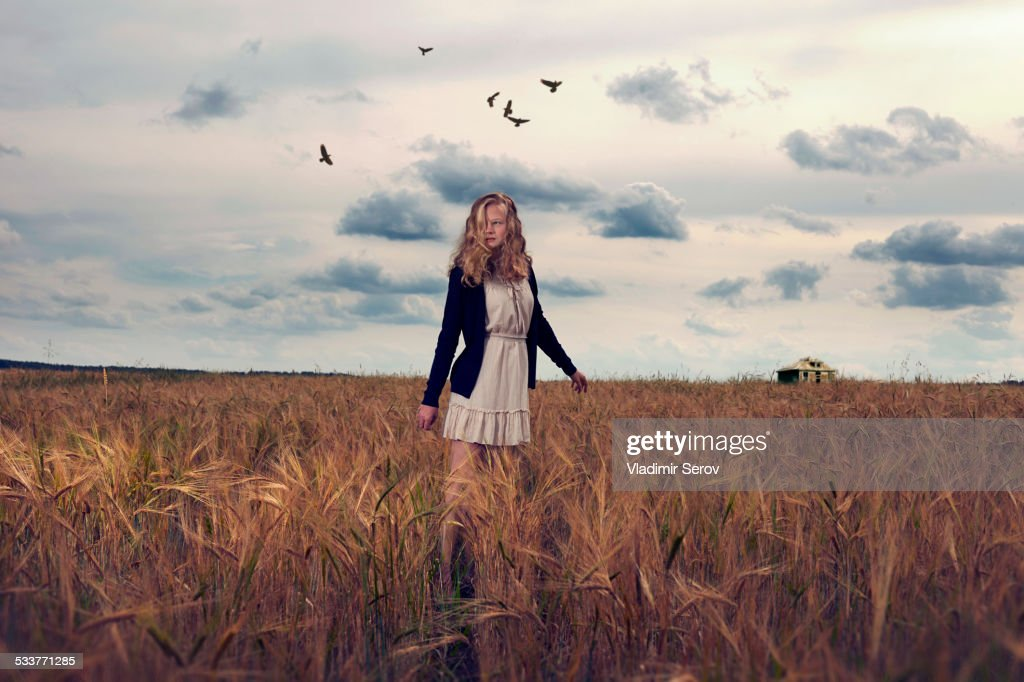 Caucasian teenage girl standing in field of tall grass : Foto stock