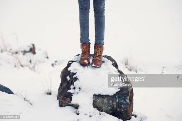 Caucasian teenage girl standing on snowy rock