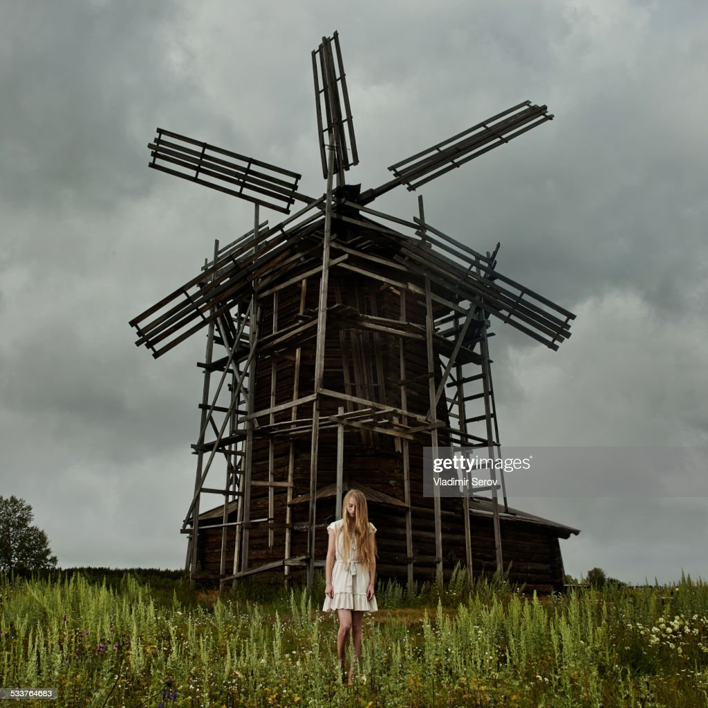 Caucasian teenage girl standing under wooden windmill : Foto stock