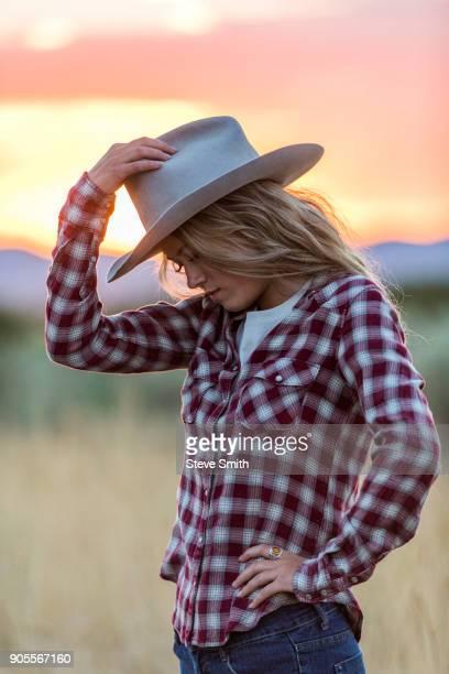Caucasian teenage girl wearing cowboy hat at sunset