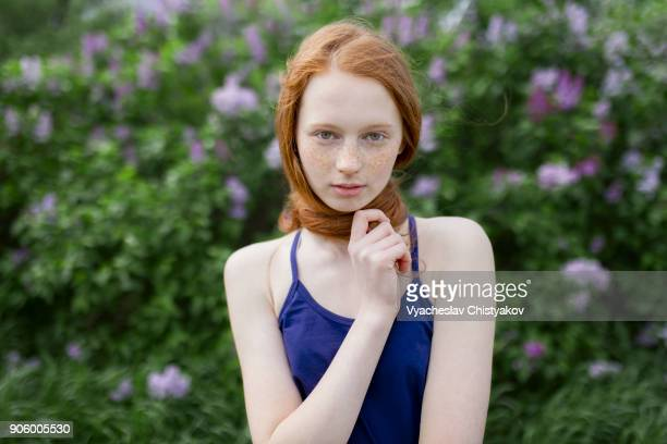 caucasian teenage girl wrapping hair around neck - jeune fille rousse photos et images de collection