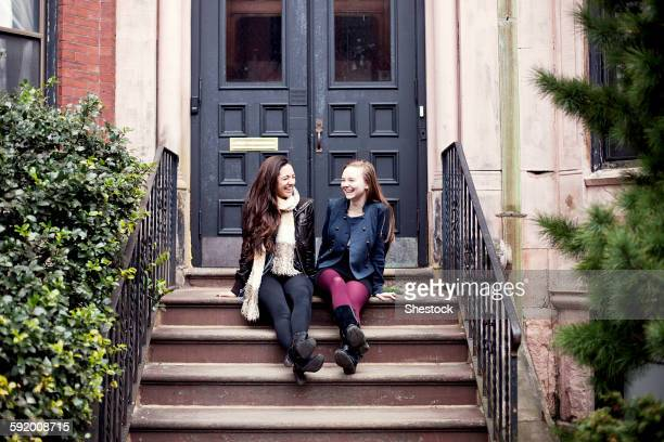 Caucasian teenage girls laughing on front stoop