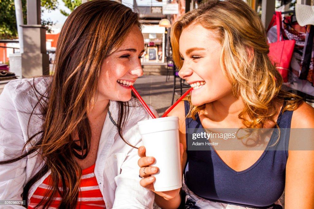 Caucasian teenage girls sharing milkshake in city : Stock Photo