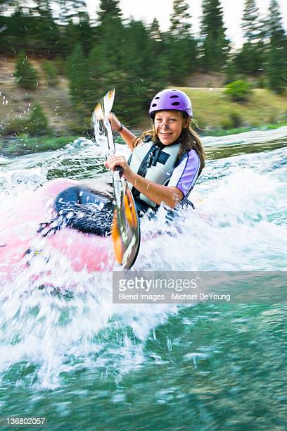 Caucasian teenager kayaking in river