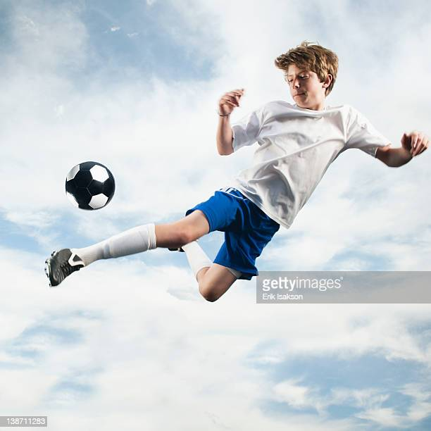 caucasian teenager kicking soccer ball in mid-air - diving to the ground stock pictures, royalty-free photos & images