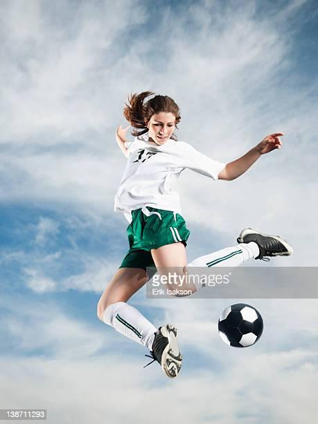 Caucasian teenager kicking soccer ball in mid-air