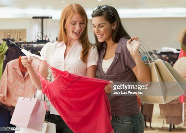 Caucasian teenagers looking at dress in shop