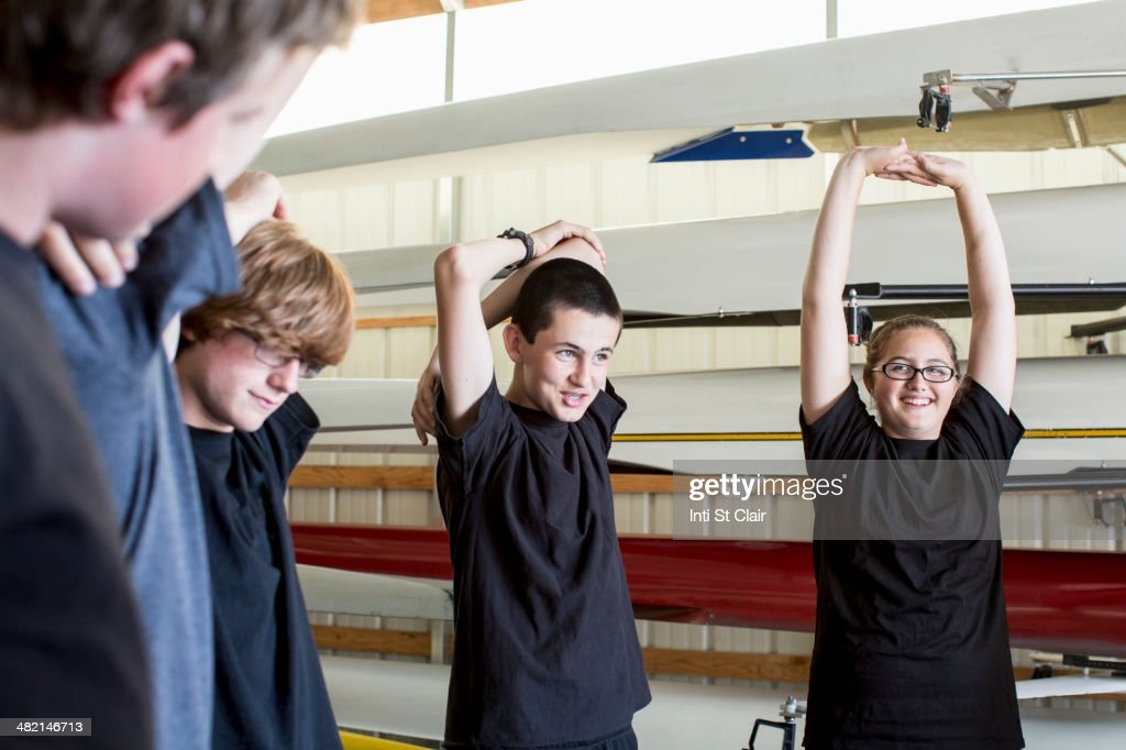 Caucasian teenagers stretching in boathouse : Stock Photo