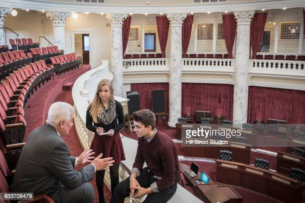 Caucasian teenagers talking to politician in capitol building