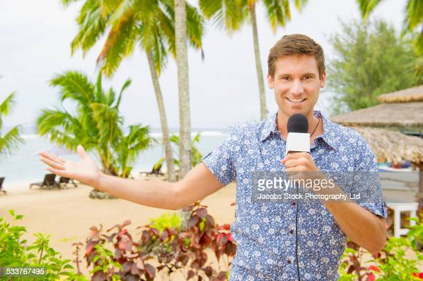 Caucasian television presenter reporting on tropical beach