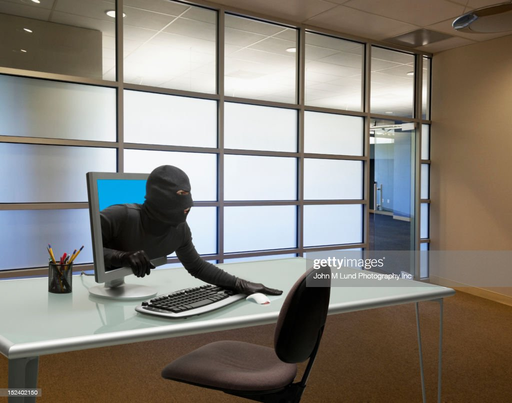Caucasian thief coming out of computer monitor in office : Stock Photo
