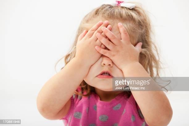 Caucasian toddler covering her eyes