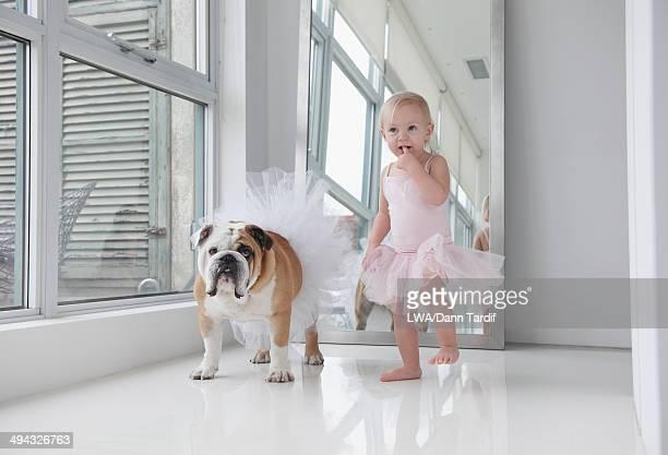 Caucasian toddler girl and dog wearing tutus