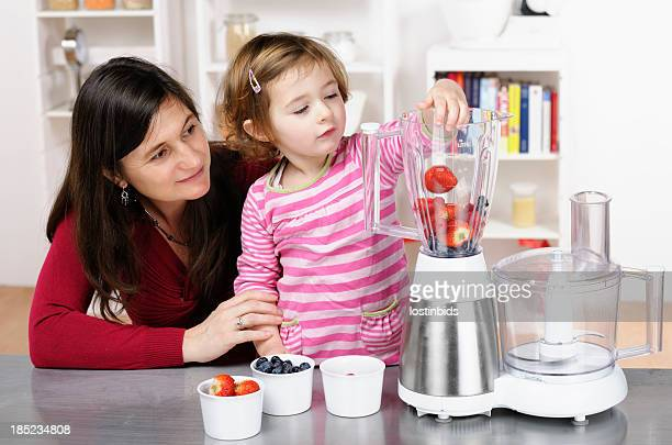 Caucasian Toddler Helping Her Mother Preparing A Smoothie