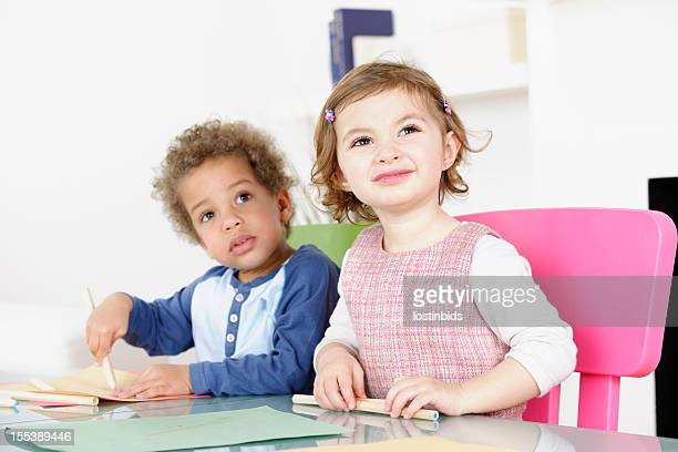 Caucasian Toddler Looking Puzzled While Peer Draws
