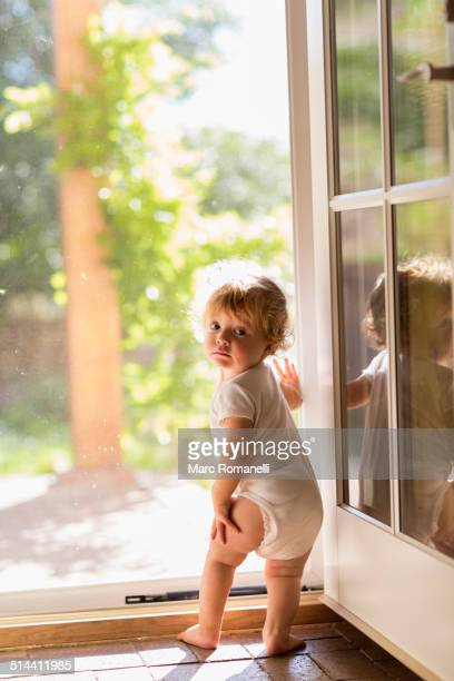 Caucasian toddler standing in doorway