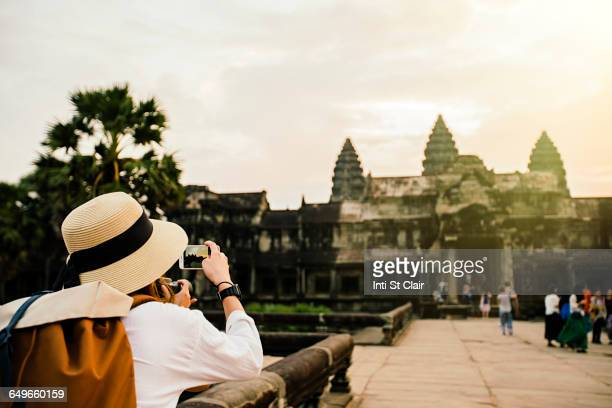 Caucasian tourist photographing Angkor Wat ruins, Siem Reap, Cambodia