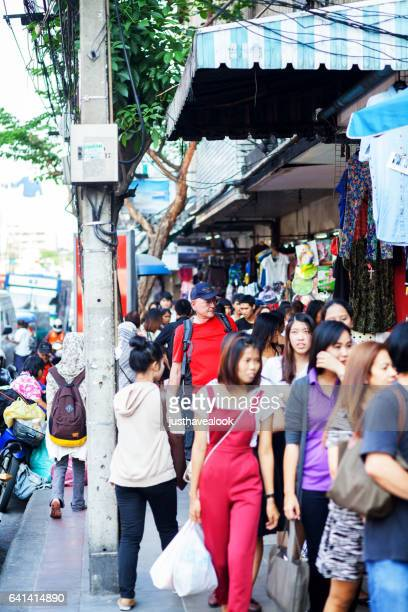 caucasian tourist senior man betweent thai people - städtische straße stock pictures, royalty-free photos & images