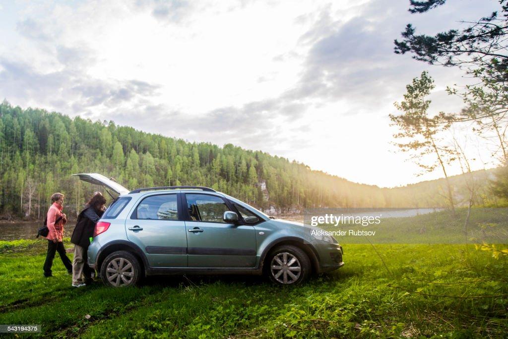 Caucasian tourists unloading car in remote landscape : Stock Photo