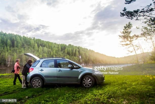 caucasian tourists unloading car in remote landscape - landvoertuig stockfoto's en -beelden