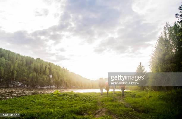 Caucasian tourists walking near river in remote landscape