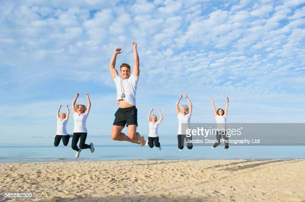 Caucasian trainer leading older women in fitness class on beach