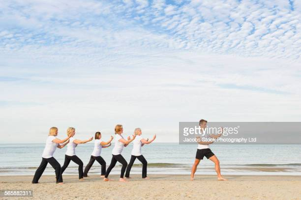 Caucasian trainer leading older women in tai chi on beach