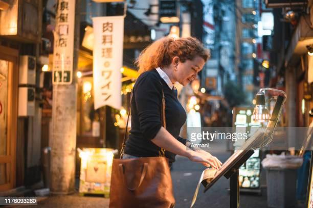 caucasian traveler checking menü außerhalb tokyo restaurant - shinjuku bezirk stock-fotos und bilder