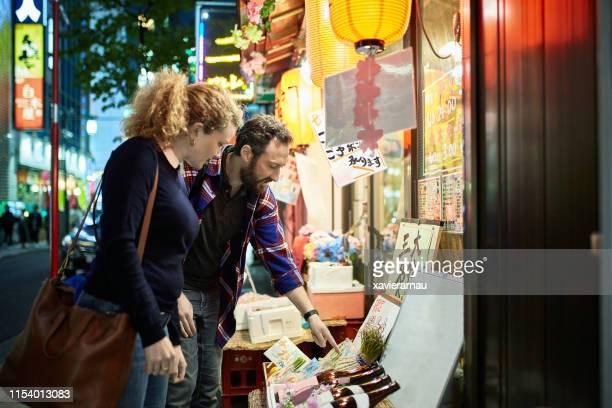 東京の白人旅行者がマーチャントについて語る - 観光客 ストックフォトと画像