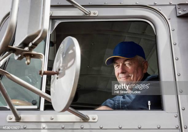 caucasian trucker sitting in semi-truck - berufsfahrer stock-fotos und bilder