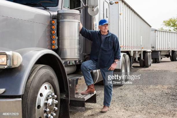 caucasian trucker standing by truck - trucking stock pictures, royalty-free photos & images