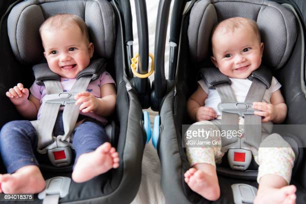 Caucasian twin baby girls in car seats