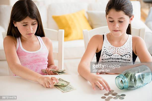 Caucasian twin sisters counting savings